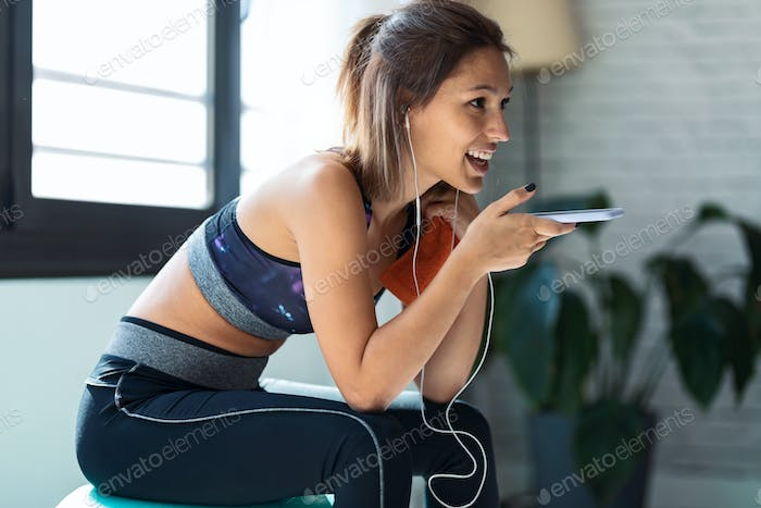 Sporty woman using mobile phone after session of exercises while sitting on fitness ball at home.