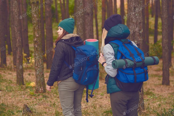 Female travelers with backpacks in the forest