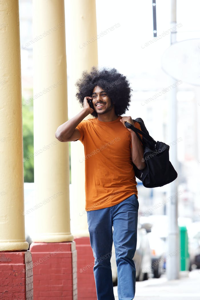 Cool guy talking on cell phone carrying bag in town