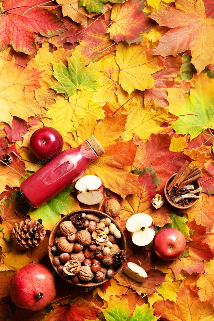 Autumn vegan and vegetarian food concept. Harvest time. Apples, pomegranate, nuts, spices, bottle of