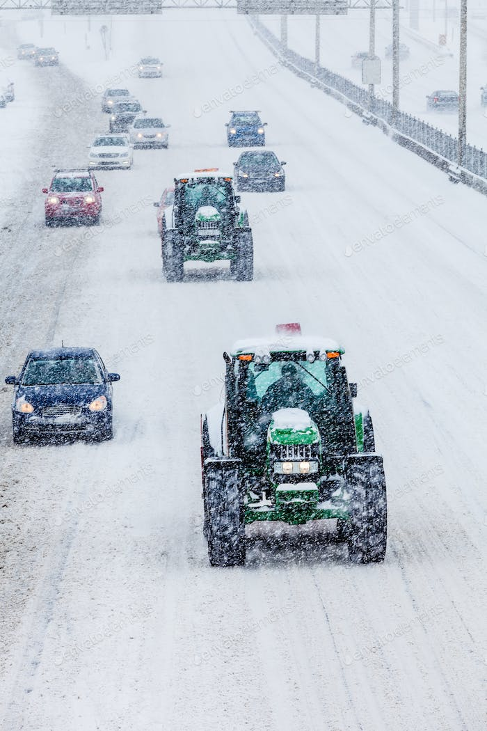 Two Snowplows and Cars During a Snowstorm