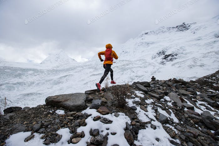 Woman trail runner cross country running on high altitude mountain ridge