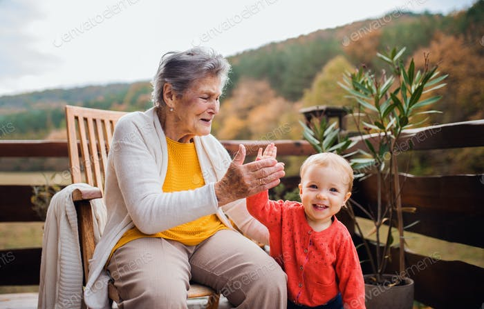 Elderly woman with a toddler great-grandchild on a terrace in autumn, giving high five.