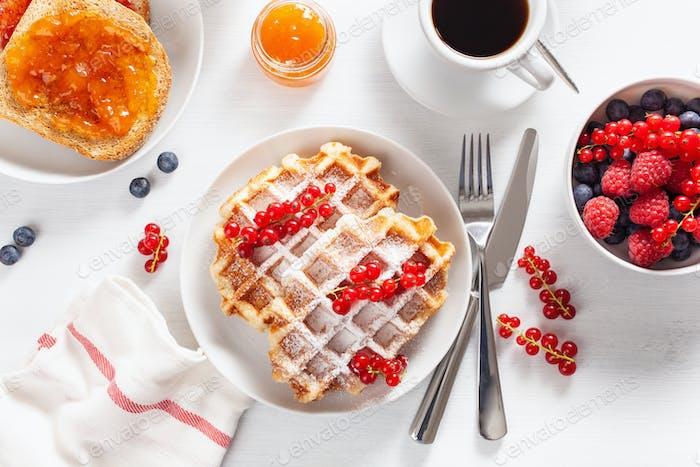 Frühstück mit Waffel, Toast, Beere, Marmelade und Kaffee. Ansicht von oben
