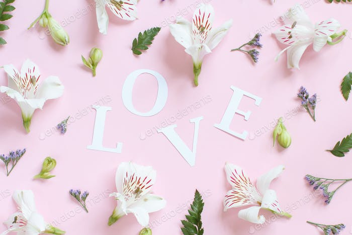 Blumen nad Wort LIEBE auf einem hellrosa Hintergrund