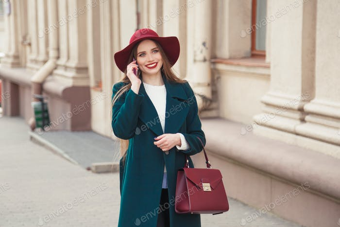 Beautiful stylishly dressed young woman smiling while talking on the phone outdoors.