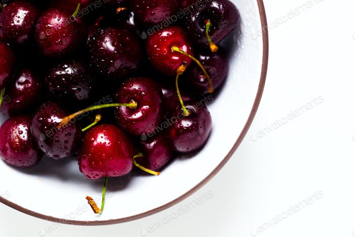 Berries of a sweet cherry with drops of water in a bowl on a white background