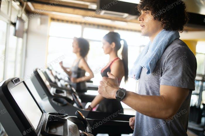 Gruppe von jungen Menschen laufen auf Laufbändern in modernen Sporthalle