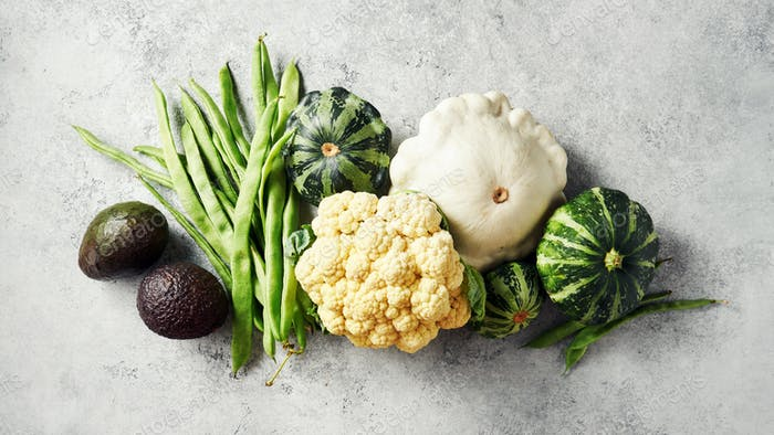 Broccoli, cauliflower, green beans, squash, and other fresh vegetables on a grey background