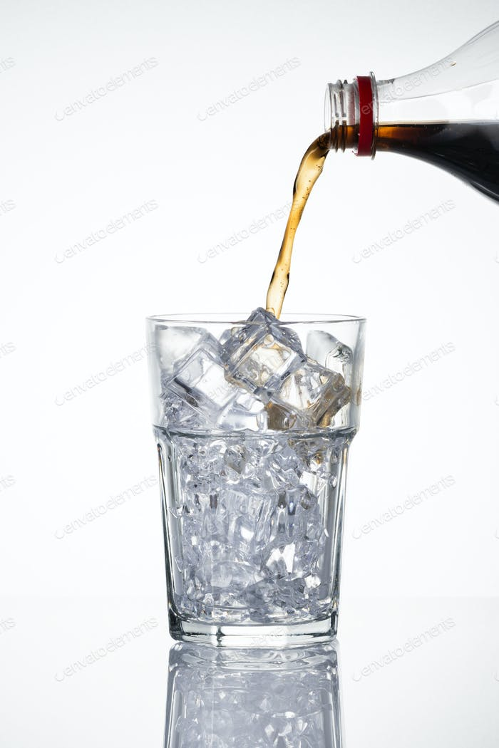 Cold carbonated drink being poured over ice cubes into a glass