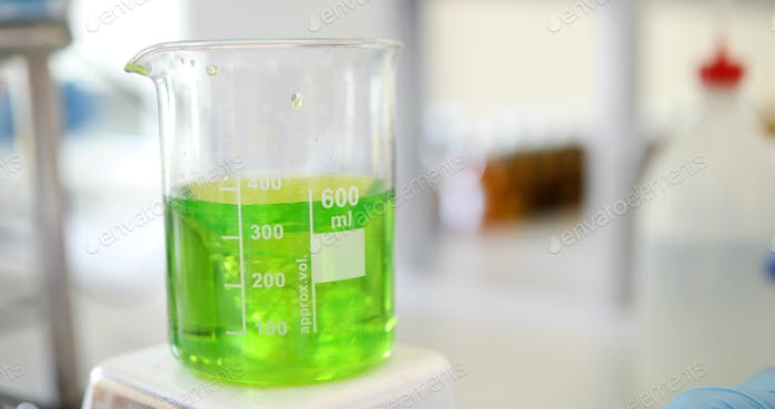 Mechanical stirring, liquid of green color is mixed in a round flask