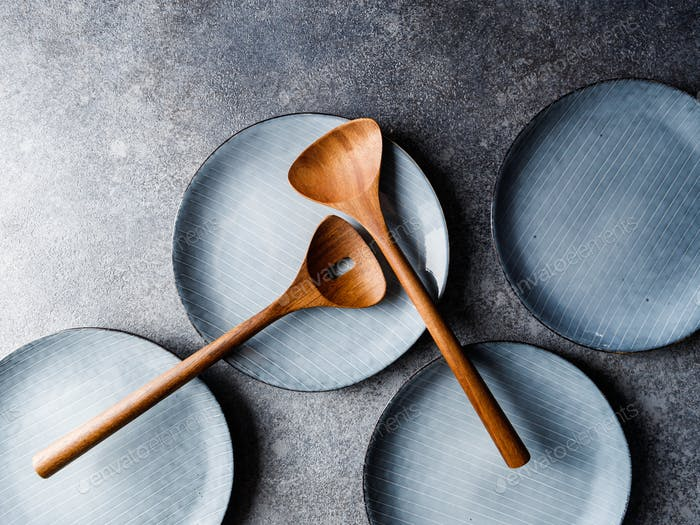 Empty blue ceramic food set with plates and wooden kitchen utensils. Minimalist style, top view.