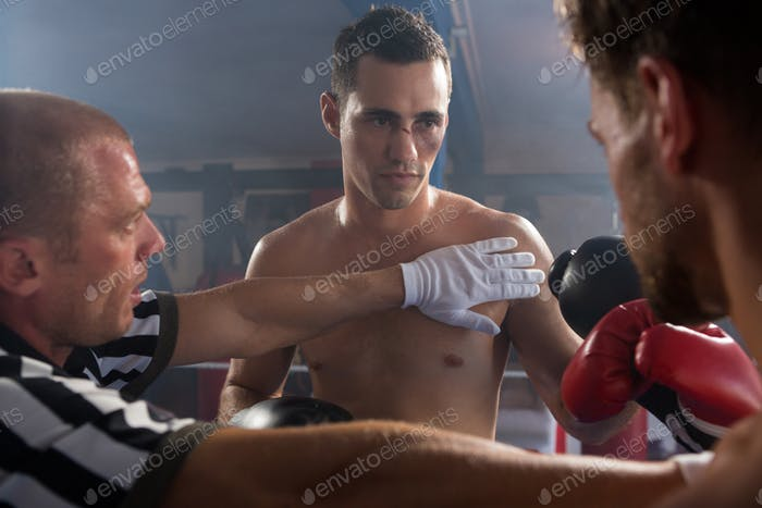 Referee stopping aggressive young male boxers