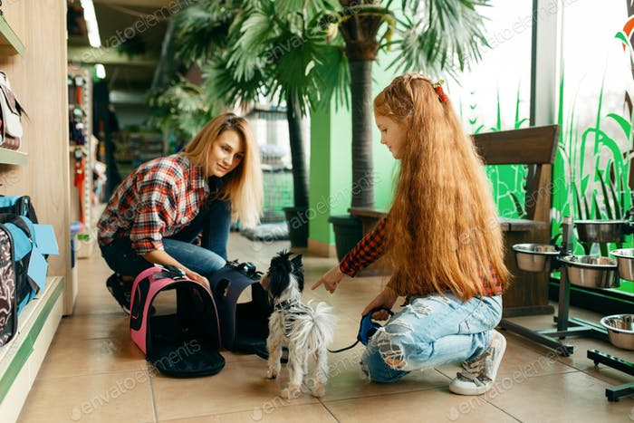 Mother with daughter choosing bag in pet store