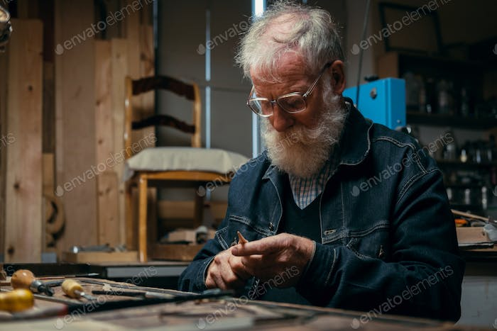 Senior wood carving professional during work