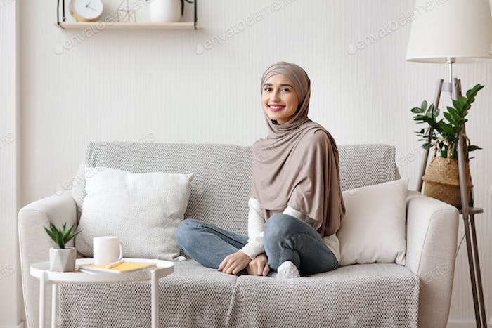 Beautiful muslim girl in hijab posing on sofa at home