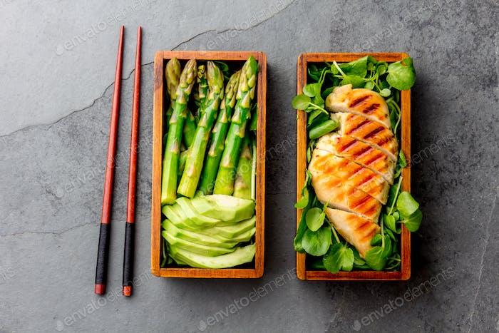 Gesundes Mittagessen in hölzerner japanischer Bento-Box, gegrilltes Huhn, Avocado, Spargel