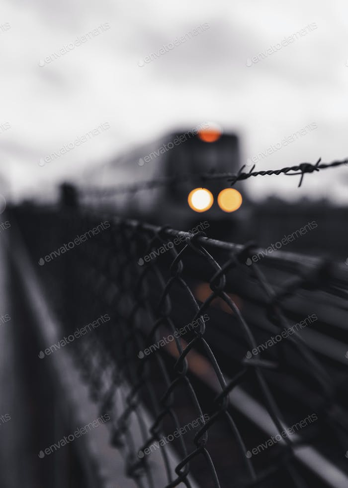 Close-up of chainlink fence and barbed wire with train in background