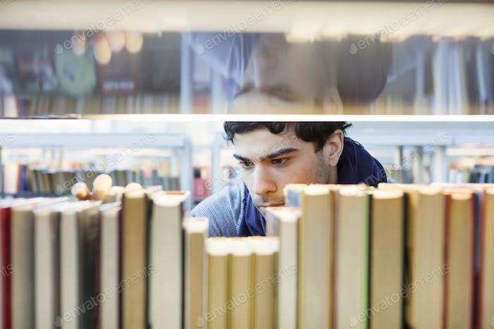 Ernsthafter junger Mann Wahl Buch in der Bibliothek