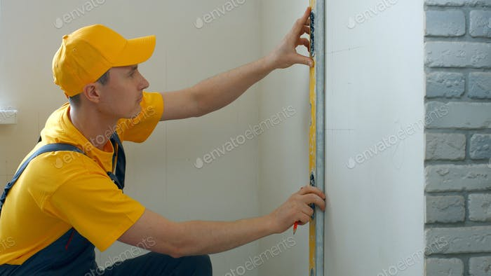 Repairman making measurement of wall.