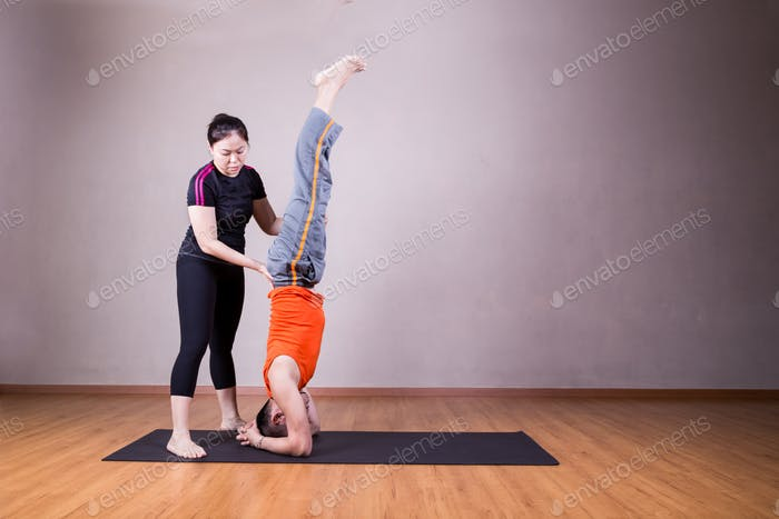 Yoga instructor guiding student perform head stand pose or Sirsa