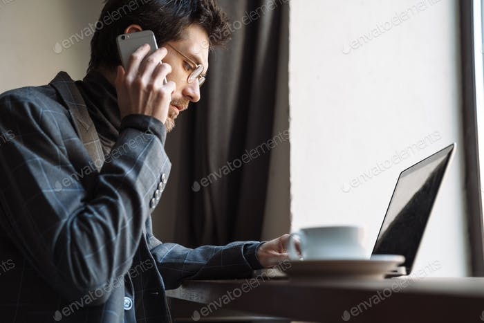 Image of focused businessman using laptop and talking cellphone