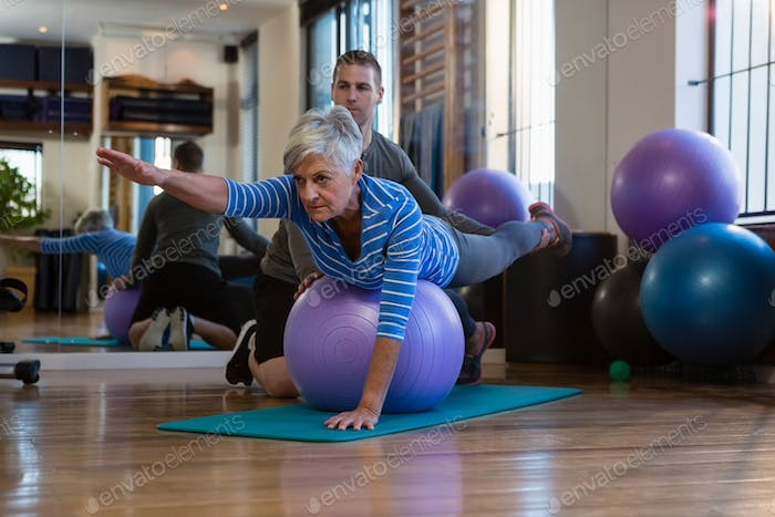 Physiotherapist assisting senior woman in performing exercise on fitness ball