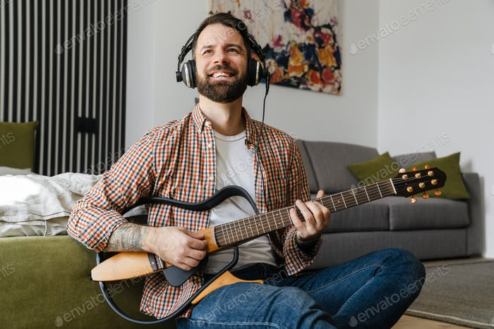 Smiling mid aged brunette bearded man playing