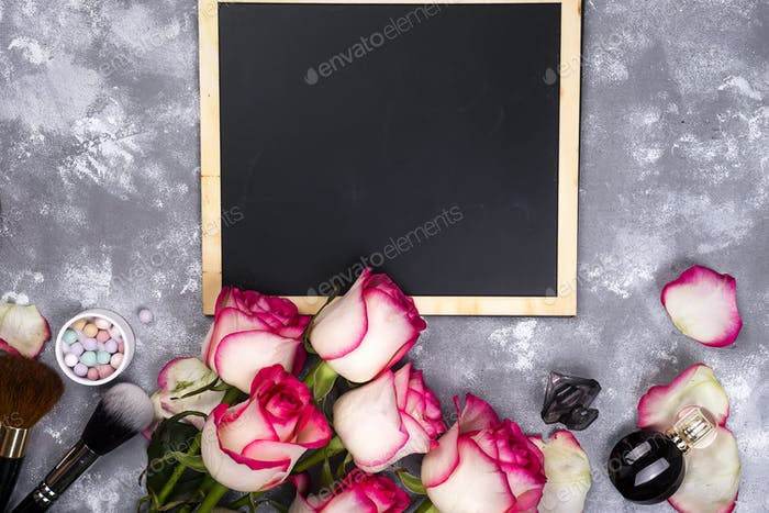 Roses and decorative cosmetics with a chalkboard