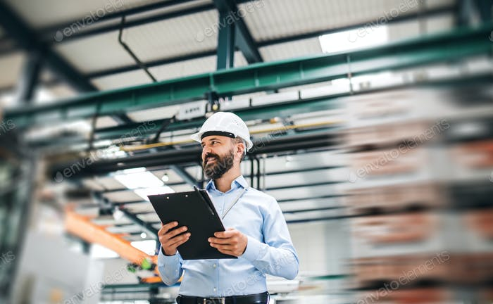 A portrait of an industrial man engineer with clipboard standing in a factory.