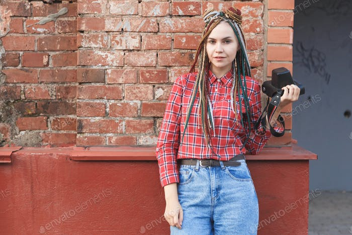 Hipster woman photographer with retro film camera on old brick wall