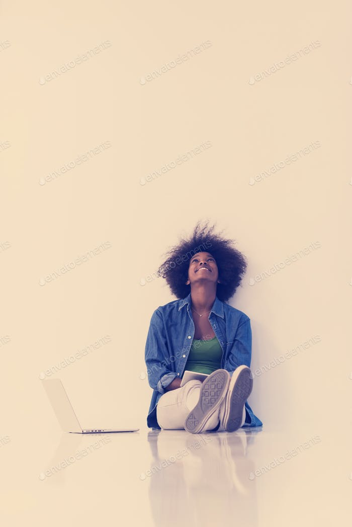 afrikanische amerikanische Frau sitzt auf dem Boden mit Laptop