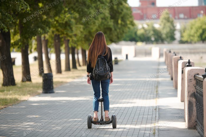 Back view of contemporary young businesswoman riding on gyroscope along road