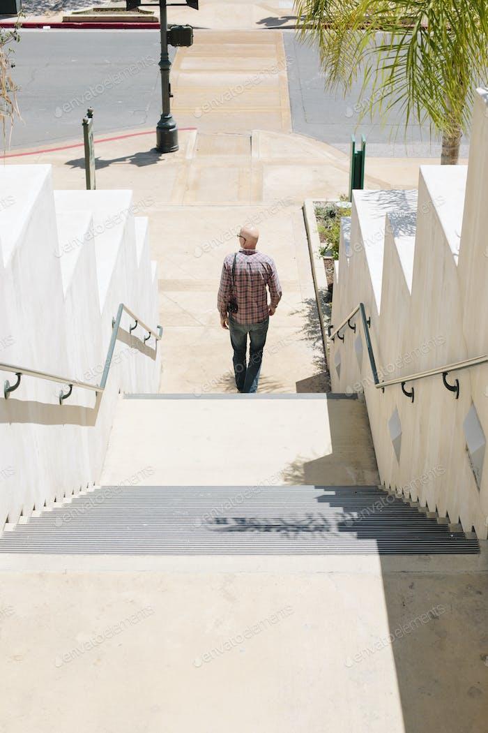 Bald man walking down a staircase.