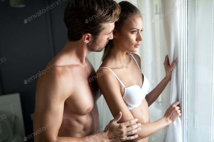 Portrait of young sensual couple in love embracing in bedroom