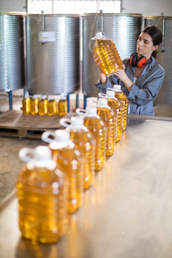 Female worker checking oil bottles
