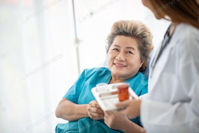 Arzt stellt sicher, dass ihre Patientin Medikamente einnimmt