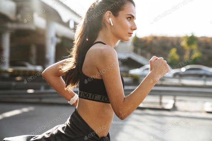 Concentrado mujer joven corriendo al aire libre