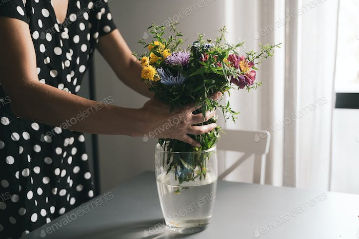 woman arranging a bouquet of flowers in a glass vase