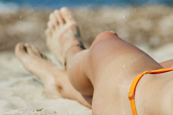 Female legs and feet on white sandy beach. Summer vacation concept