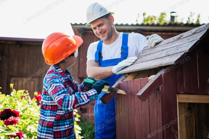 Handsome teenage carpenter and his father in protective glasses are smiling while working with wood