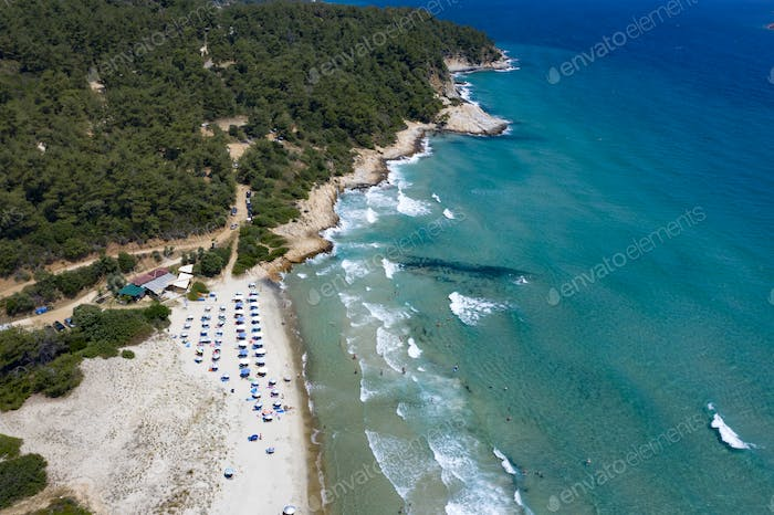 Thassos seaside beach with turquoise water and big waves aerial view.