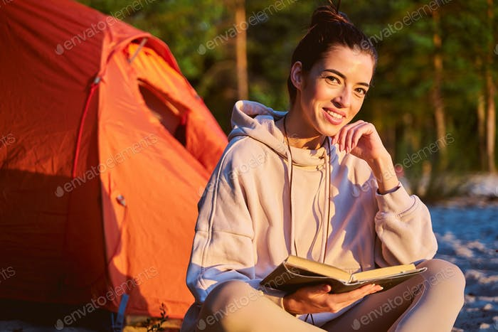 Cheerful female traveler reading book on sunny day