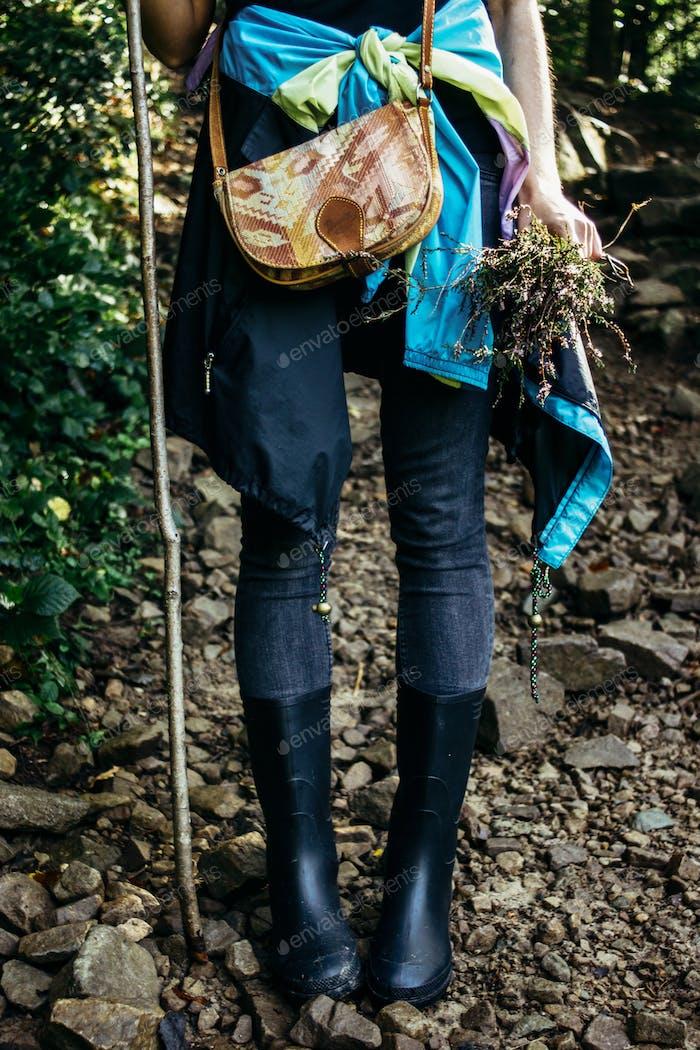 viajero chica con estilo de pie en el bosque soleado en las montañas