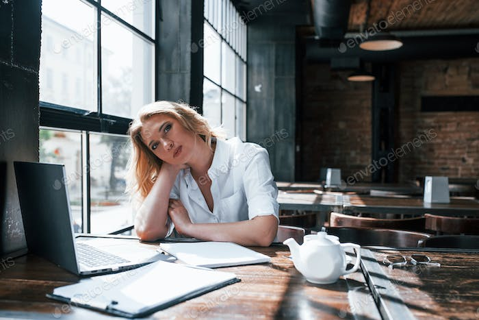 Businesswoman with curly blonde hair indoors in cafe at daytime