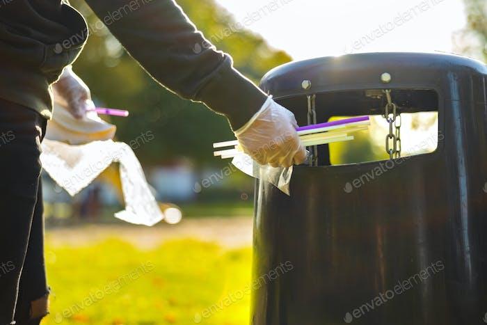 Volunteer putting straws in garbage bin at park