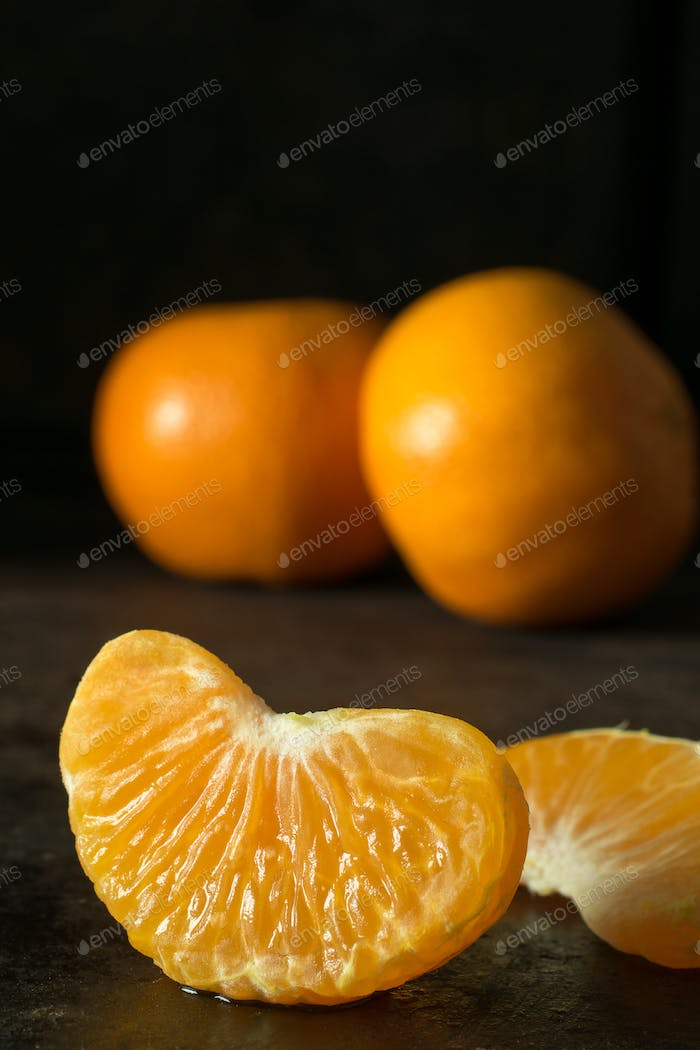 A close up of a juicy segment of an orange tangerine