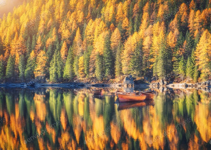 Wooden boats on Braies lake at sunrise in autumn