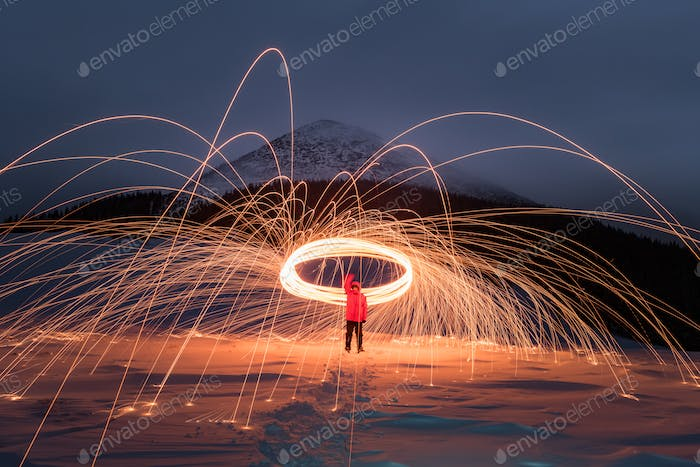 Fire show with lot of sparks in night winter mountains