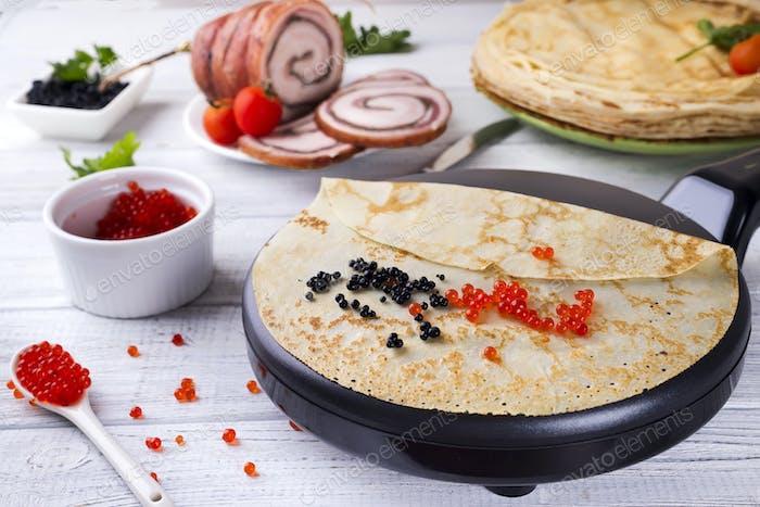 Pfannkuchen mit rotem Kaviar auf Teller.
